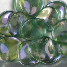 Czech glass rose petals in Aqua Clarit, 14mm x 13mm. Petal-shaped drop beads in transparent green-blue, with a shimmery lilac finish. UK seller.