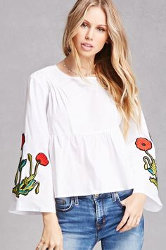 A woven top featuring a round neck, pintucked yoke detail, long bell sleeves with floral patches, a button back keyhole, a shirred waist, and a billowy silhouette.<p>- This is an independent brand and not a Forever 21 branded item.</p>