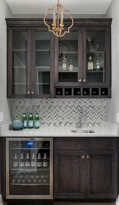 Exquisite brown wet bar boasts dark brown shaker cabinets accented with brass no. Exquisite brown wet bar boasts dark brown shaker cabinets accented with brass nobs and fitted in a Shaker Kitchen, Shaker Kitchen Cabinets, Home Bar Designs, Small Bars For Home, Basement Remodeling, Kitchen Remodel, Shaker Cabinets, Bars For Home, Diy Kitchen
