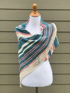 This crochet asymmetrical shawl pattern is perfect for for wrapping around your shoulders on a summer evening. This asymmetrical shawl pattern creates a beautiful vintage style asymmetrical shawl that can be worn as a gentle shoulder wrap or light weight summer scarf. With textured stripes mixed with gorgeous lace, you will be wearing this shawl all summer long! p.s. It would make a beautiful gift!  Crocheted with a mix of basic stitches and a feminine lacy edging, this asymmetrical shawl…