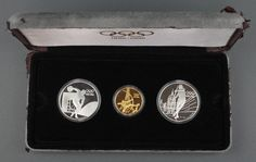 Lot 830g, A cased 1996 Olympic commemorative coin set comprising 2 silver crowns - javelin thrower and discus thrower 7 grams and a 22ct yellow gold ditto - the archer 16.8 grams, cased est £700-800