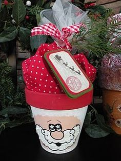 Terra Cotta Pots with a little Gingerbread and a Joyful Santa!  Terra Cotta Pots are hand painted and embellished with a gift inside wrapped in coordinating fabrics.  Put cookies, chocolates, gingerbread treats, Christmas treats inside.  Tie with ribbon and tags..makes a great neighbor gift!  (I was given the Santa Terra Cotta Pots from  dear friends and neighbors).