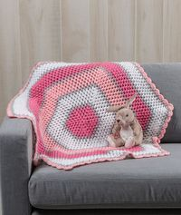 Sweet Baby Hexagon Blanket Free Crochet Pattern in Red Heart Yarns - Pink and grey tones are a sweet combination for this cozy puff-stitch baby blanket. This easy pattern is crocheted from the center outward in hexagon-shaped rounds. This is a favorite way to create a blanket with few ends to weave in when you are done crocheting.