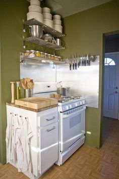 This small kitchen uses stainless steel shelves from Ikea to create storage above the range and stacked round storage boxes to house all the goodies. | Tiny Homes