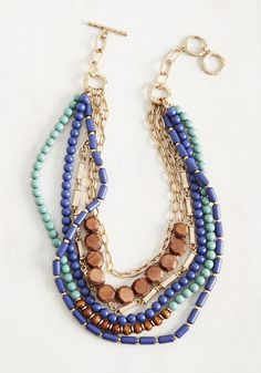 "Wondering if you can sport this statement necklace with that look? The answer is always, ""Yes!"" Layer this accessory over any ensemble to flaunt its layered strands of dusty blue and lake blue beads, golden chains, and wooden accents - eliciting ""ooh""s and ""ahh""s everywhere you go"