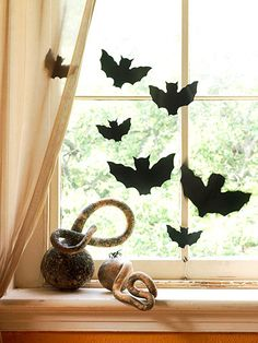 From Better Homes & Gardens Batty Silhouettes - Cut several sizes of bats from black poster board. Tape fishing line at different spots on the backs & head; hang the lines from a curtain rod or cup hooks. These will be in my windows this year!