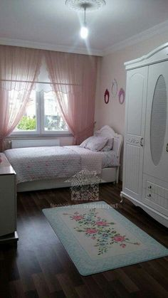 Cottage chic bedroom with white painted armoire, blush pink walls and curtains, floral rug and bedding.