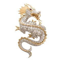 "McTeigue Diamond Gold Platinum Dragon Brooch. Circa 2000 McTeigue Platinum and 18K Yellow Gold Dragon Brooch, measuring 2"" in length and 1.25"" wide. Set with approximately 4 Carats of round brilliant cut diamonds and ruby set eyes. Very finely detailed and features an articulated tongue. Can also be worn as a pendant. Offered by N. Green and Sons/1stDibs. Sold."