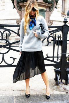 Natalia Georgala of Twin Fashion Blog wearing a black chiffon pleated dress (worn as skirt), with a basic gray sweatshirt, neck scarf and black pointed-toe pumps