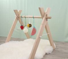 Wooden baby gym with 4 toys, play gym, activity center, nursery decor, crochet rattle, shower newborn gift, playgym, Montessori. Our wooden play gym with a bee and 3 hanging fruits rattles is a must have for new parents because it is great for babies to play and stimulate development of their visual and motor skills. Our play gym: ♥ Perfect for any hanging baby's toys. ♥ Made of unfinished alder wood and sanded to be silky smooth. ♥ Free of any chemicals and safe for a baby. ♥ Has a basic...