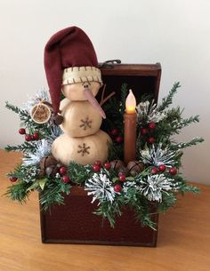 This medium sized vintage chest features a stock hat snow fella and is embellished with pine, frosted Ming, glittery leaves, rusty jingle bells and a wax dipped, battery operated flicker candle. Primitive Christmas, Christmas Snowman, Rustic Christmas, Winter Christmas, Christmas Time, Christmas Wreaths, Christmas Ornaments, Christmas Floral Arrangements, Christmas Centerpieces