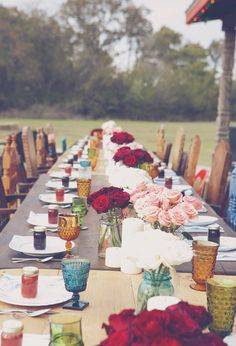 Mismatched chairs, frosted jewel tone glasses, plus lush red roses make this a lovely outdoor bohemian spread.