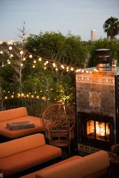 A Guide to L.A.'s West Hollywood Neighborhood: La Petite Ermitage Rooftop Deck with Brick Fireplace and View of Downtown LA | coveteur.com