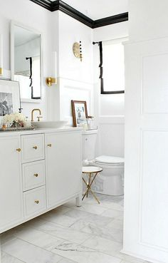 accents of black in a white bathroom with gold trims