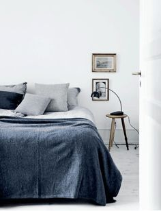 Grey and white bedroom in the lovely Copenhagen apartment of an architect. Tia…