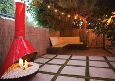 A modern take on a vintage classic adds warmth to this quaint backyard. EcoSmart Fire transformed this retro wood-burning fireplace into a clean-burning alternative with the Burner One from EcoSmart Fire. Concrete pavers and synthetic grass create a no-fuss entertaining area while the built-in seating provides even more space to lounge.