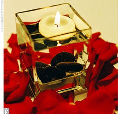 wedding decoration idea. love the red petals and black rocks