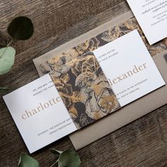 """A studio favorite, the timeless, romantic Charlotte has a unique horizontal shape and an ornate metallic floral bellyband. This 3.875"""" x 9.25"""" two-ply invitation features gold metallic and charcoal matte thermography."""