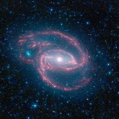 Black Hole Creates Eye in Middle of Cosmic Storm. In the Spitzer image of NGC 1097, infrared light with shorter wavelengths is blue, while longer-wavelength light is red. - Credit: NASA/JPL-Caltech/The SINGS Team (SSC/Caltech)