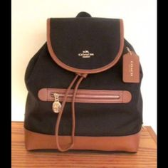 """*NWT* Authentic Coach Sawyer Backpack *NWT* Authentic Coach Sawyer Backpack in Black.  Features: * Black twill fabric with saddle (brown) leather trim * Measures approx. 11 1/4"""" (L) x 12 3/4"""" (H) x 4 1/4"""" (W) * Coach embossed gold-tone hardware * Leather bottom * Interior fully lined  * Two internal leather-trimmed slip pockets on front wall * One internal zippered pocket on back wall Coach Bags Backpacks"""
