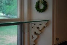 Build kitchen window shelf held up with antique corbels.