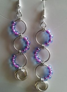 Funky and fun chain mail earrings, made with aluminum jump rings and purple lined translucent glass seed beads in a wave pattern, finished off with a eternity ring. The other photo is of my patriotic colored wave pattern. I can make these in a variety of colors so let me know what you are looking for. If I dont have the colors you need in stock it will be $2 more per pair. These earrings measure about 1.75 from the top jump ring down. All of my earrings have nickel free ear wires.