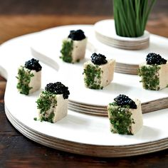 In an architectural take on the classic combination of blini and caviar, the blini are layered with creme fraiche, then cut into bite-size pieces and topped with caviar.