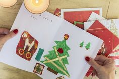 Woman hands with red fingernails holding beautiful Christmas card made by a child on wooden table where more cards are placed to be written. Candle lit Christmas decoration adorning the scene.