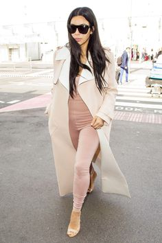 Kardashian opted for comfort in a blush-toned leotard that hugged her curves and showcased her cleavage. She elevated the unusual piece together by throwing on matching ankle-strap sandles, an oversized coat, and dark tinted sunglasses.
