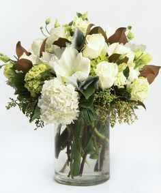 Winter Wonderland A seasonal favorite, this stunning collection of all whites and creams - including amaryllis, roses and lisianthus - is gathered in our signature cylinder vase and accented with seasonal greens such as magnolia and white pine.