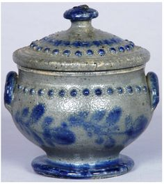 "Exceedingly Rare and Fine Cobalt-Decorated Sugar Bowl with Applied Rosette Decoration and Lid, attributed to Emanuel Suter, Rockingham County, VA, circa 1851, squat, ovoid jar with rounded handles and dramatic foot, decorated with two clover-like flowers on each side, cobalt-brushed foot and handles, and applied molded rosette decoration below the rim on both sides.  Height without lid 3 1/2"" ; Diameter across top 3 7/8""."