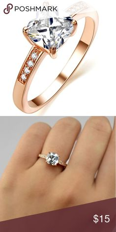Rose Gold Cubic Zirconia Engagement Ring This gorgeous engagement ring features a cubic zirconia diamond in an 18k rose gold setting with a row of 4 stones on either side. AAA Cubic Zirconia with brilliant long lasting shine. Brand new, perfect condition. Jewelry Rings