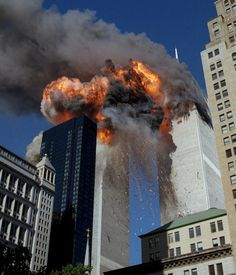 Smoke, flames and debris erupt from one of the World Trade Center towers as a plane strikes it on Sept. 11, 2001. The first tower was already burning following a terror attack minutes earlier. Terrorists crashed planes into the two buildings and collapsed both towers. (Chao Soi Cheong/AP)