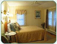 Room 9: Deluxe Room  Large sunny room with a queen bed, twin Murphy bed (which is closed up in the wall when not in use), flat panel TV/DVD, and private tub & shower bath overlooking perennial gardens, Merriman State Forest, and Black Cap Mountain. Decorated with pale yellow and white striped wallpaper and features a wide pine floor.