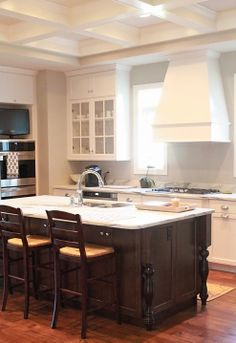 kitchen with white marble, stained island, cream cabinets and coffered ceiling