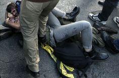 I due manifestanti sono abbracciati a terra, lui protegge lei durante gli scontri e le cariche tra piazza Barberini e via del Tritone. Mentre i ragazzi sono bloccati a terra da un poliziotto, lui con la fronte leggermente insanguinata, un altro agente sale sul fianco della ragazza urlante  (foto di