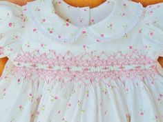 Adorable baby girl hand smocked dress with dainty pink rosebuds tossed on a pure white background. It is a classic style with raised yoke,