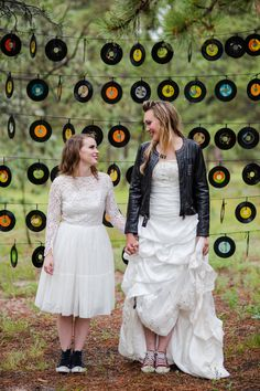 Rocker same sex lesbian wedding with rock n roll music theme.  Record album wall, leather jacket, hi lo wedding dress.  Record plate charges, snare drum cupcake stand, red piano.   Rachael + Emily Photos by Katie Corinne Photography