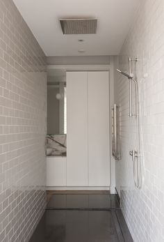 Walk through shower with light gray subway ceramic tile