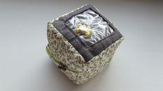 Bonjour, Aujourd'hui, je vous propose de réaliser un petit cube d'éveil avec le matériel de la box. Pour cela, vous aurez besoin : du tissu liberty de la feutrine du fil à broder gris e…