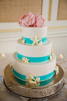 Gorgeous beach wedding cake with turquoise ribbon, edible starfish and seashells and topped with a pink peony flower.