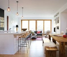 """Airy-light filled hom  """"Thick Corian countertops and wire pendant lights create a modern look in the open concept living, dining and kitchen space. Rattan bar stools and off-cut oak floors add softness. """""""