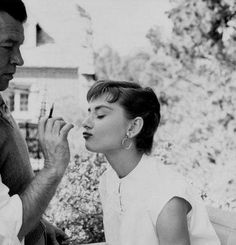 Audrey Hepburn gets a last minute touch up from makeup artist Wally Westmore on the set of Paramount's Sabrina 1954