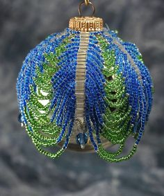 Beaded Ornament Cover. 30 bugle beads in 6? Rows. Drape seed beads between bugles. Add taddle at bottom of bugles. Can leave 6 bugles at bottom without beads draped. Bugles can be sd many as you wish. Blue and green one about 2 thirds of lengthof ball. Tan and brown on site they go to the bottom of the ball.