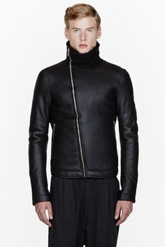 RICK OWENS //  Black leather and shearling jacket  32232M032003  Long sleeve thick leather jacket in black. Stand collar trimmed in tonal suede trim. Angled zip closure and zippered welt pockets at front. Shearling interior. Tonal stitching. Body: 100% lamb shearling. Sleeve lining: 100% cupro. Specialty cleaners. Imported.  $4300 CAD