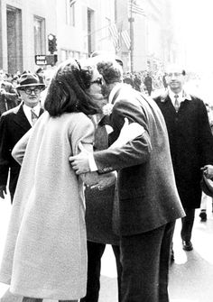 Senator Robert Kennedy gets a surprise kiss from his sister in law, Mrs. John F. Kennedy, as he marches up New York's Fifth Avenue in the St. Patrick's day parade.