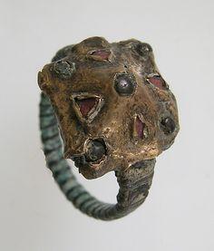 7ème siècle, franc, nord de la France. bague, bande d'alliage de cuivre?, lunette en argent recouvert d'or, grenat ou pâte de verre