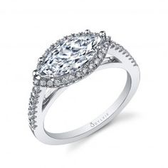 This magnificent white gold engagement ring expresses romanticism as well as modernism in the way the 1 carat marquise cut diamond center is set in a west-east position and accentuated by a shimmering halo of round brilliant diamonds. Cascading diamonds d Marquise Ring, Marquise Diamond Settings, Marquise Cut, Buying An Engagement Ring, Diamond Engagement Rings, Diamond Rings, Thing 1, Beautiful Rings, Ring Designs