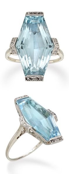 An Art Deco aquamarine and diamond ring, circa 1920. The lozenge-shaped faceted aquamarine weighing 10.96 carats, a row of four rose-cut diamonds set to each end and side, set to a platinum mount with ornate scroll pierced gallery, with fine tapered D-section platinum shank and cheniered shoulders. #ArtDeco #ring