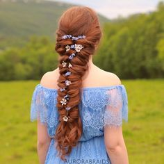 Fair-skinned copperhead in sky lace off-shoulders dress w/ beblossomed waistlength fishtail braid; lush green grass & forested hills beyond